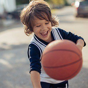 Smiling little boy playing basketball