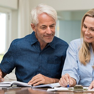 Older man and woman reviewing dental insurance paperwork