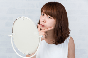 Woman looking at jaw alignment in mirror