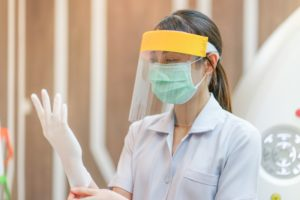 dentist in Carrollton putting on PPE before treating a patient