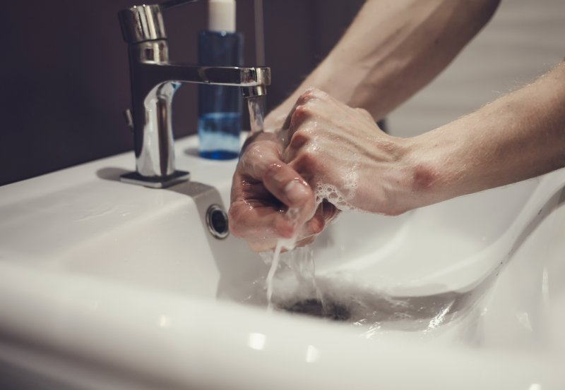 Close-up of dental team member washing their hands