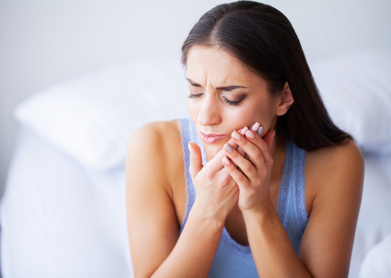 a woman seated on the side of her bed holding her cheek and cringing in pain