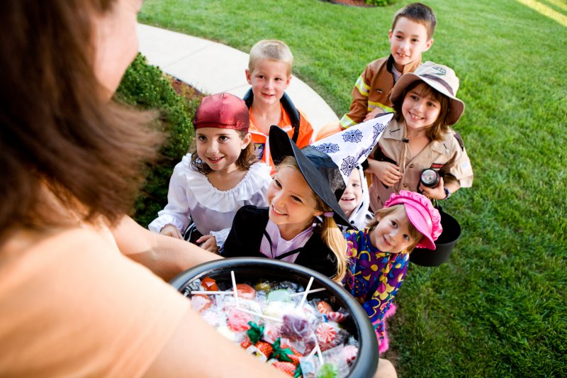 Group of kids smiling while trick-or-treating