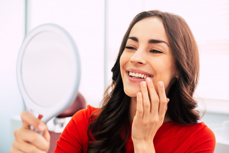 a young woman wearing a red blouse and admiring her new smile in the mirror
